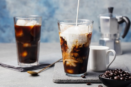 Ice coffee in a tall glass with cream poured over and coffee beans on a grey stone background 스톡 콘텐츠