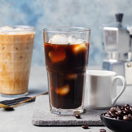 Ijskoffie in een hoog glas en koffiebonen op een grijze steen achtergrond Stockfoto