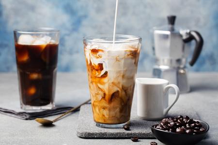 IJskoffie in een lang glas met over gegoten room en koffiebonen op een grijze steenachtergrond