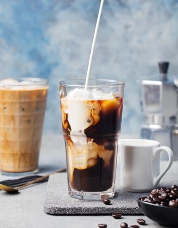 Eiskaffee in einem hohen Glas mit Sahne übergossen und Kaffeebohnen auf einem grauen Stein Hintergrund