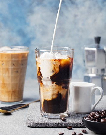 poured: Ice coffee in a tall glass with cream poured over and coffee beans on a grey stone background Stock Photo