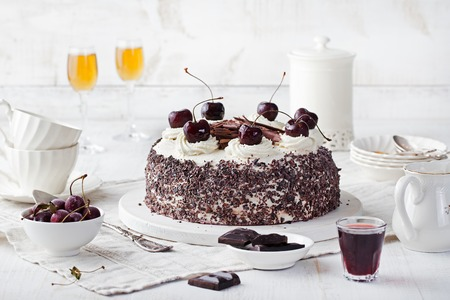 Black forest cake ,decorated with whipped cream and cherries Schwarzwald pie, dark chocolate and cherry dessert on a white wooden background Stockfoto