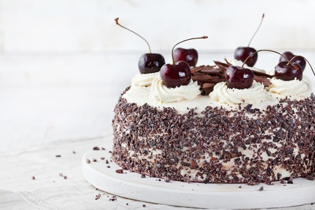cakes and pastries: Black forest cake ,decorated with whipped cream and cherries Schwarzwald pie, dark chocolate and cherry dessert on a white wooden background Stock Photo