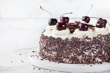 tortas de cumpleaños: torta del bosque negro, decorado con crema batida y cerezas tarta Selva Negra, chocolate negro y postre cereza en un fondo de madera blanca