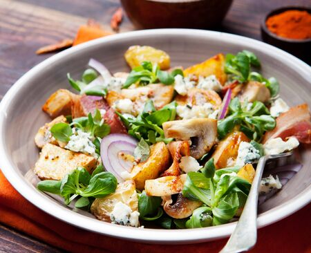 Potato salad with bacon, mushroom on orange napkin