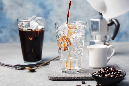 Ice coffee in a tall glass and coffee beans on a grey stone background. Archivio Fotografico