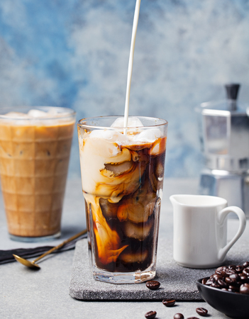 Ice coffee in a tall glass with cream poured over and coffee beans on a grey stone background.