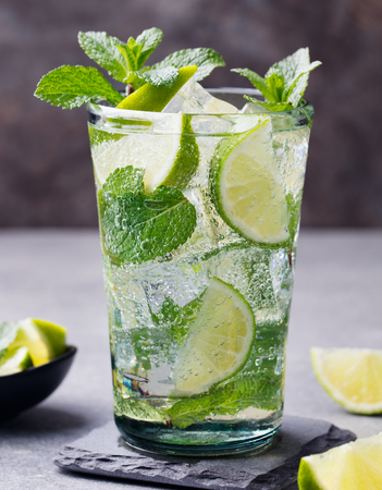 caribbean: Mojito cocktail with lime and mint in highball glass on a grey stone background. Stock Photo