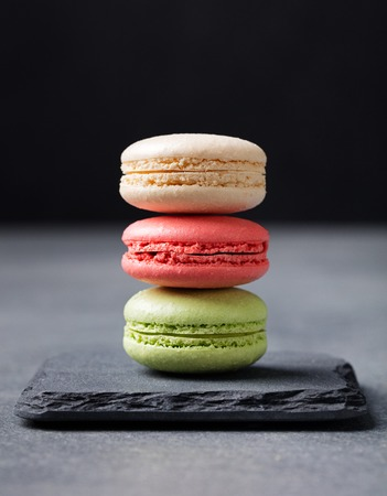 Colorful French Macarons on the slate stone background Copy space. Stock Photo