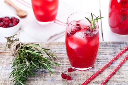 fizz: Cranberry and rosemary lemonade, cocktail, fizz on a wooden background.