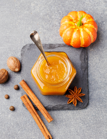 Pumpkin confiture, jam, sauce with spices on stone table Top view. Stock Photo