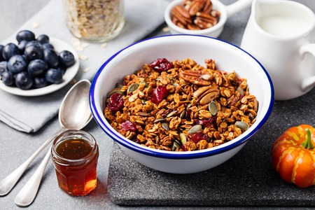 maple syrup: Healthy breakfast. Fresh granola, muesli with pumpkin,pecan nuts,cranberries and maple syrup in white bowl