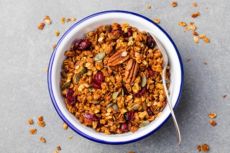 oatmeal bowl: Healthy breakfast. Fresh granola, muesli with pumpkin,pecan nuts,cranberries and maple syrup in white bowl. Copy space. Top view.