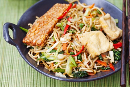 Mi goreng,mee goreng Indonesian cuisine, spicy stir fried noodles with tempeh and assortment of asian sauces Stock Photo