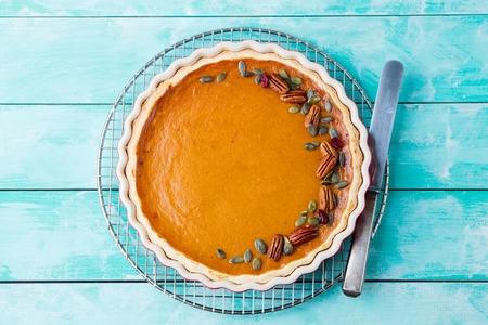 butternut: Tasty pumpkin pie, tart made for Thanksgiving day in a baking dish on a cooling rack. Turquoise wooden background