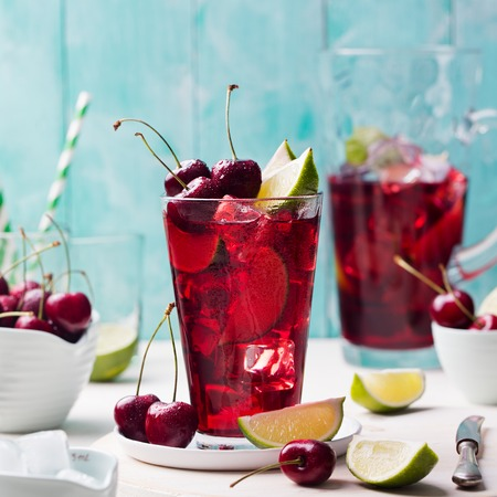 infused: Cherry cola, limeade, lemonade, cocktail in a tall glass on a white, turquoise background Copy space
