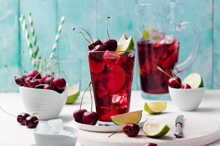 Cherry cola, limeade, lemonade, cocktail in a tall glass on a white, turquoise background Copy space