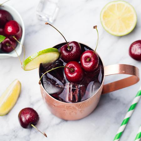 Koude Cherry Moscow Mule cocktail met gember bier, wodka, kalk Marmeren achtergrond kopie ruimte Bovenaanzicht Stockfoto