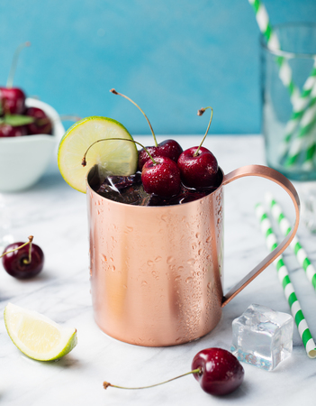 Cold cherry Moscow Mules cocktail with ginger beer, vodka, lime Marble background. Copy space
