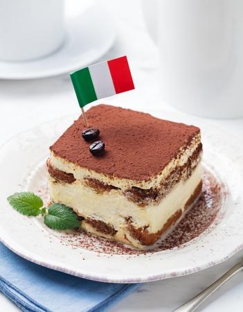 amaretto: Tiramisu, traditional Italian dessert on a white plate with Italian flag. Stock Photo
