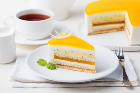 Passion fruit cake, mousse dessert with tropical flavor on a white plate with cup of tea