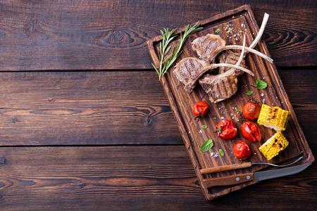 Lam ribben gegrild op snijplank met geroosterde groenten. Bovenaanzicht kopieer ruimte Stockfoto