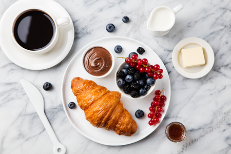 Croissant with fresh berries, chocolate spread and butter with cup of coffee on a marble texture background. Top view Stockfoto