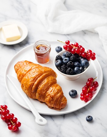 plates of food: Croissant with fresh berries, chocolate spread and butter with cup of coffee on a marble texture background. Top view Stock Photo