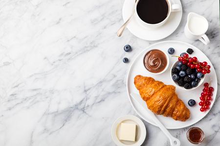 Croissant con bayas frescas, crema de chocolate y la mantequilla con la taza de café sobre un fondo de textura de mármol. Vista superior del espacio de copia