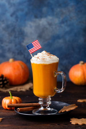 Pumpkin spice latte, smoothie with whipped cream on top on a wooden background. Copy space
