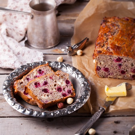 kinfolk: Cranberry and hazelnut wholegrain bead, loaf on a wooden background. Rustic style. Wooden background