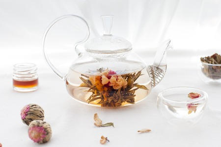 Traditional asian floral tea in a glass teapot on white textile background Stock Photo