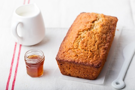 Cake, tea loaf with jam and cream on a textile white background.