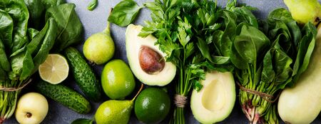 Green vegetables and herbs assortment on a grey stone background. Top view Stock Photo