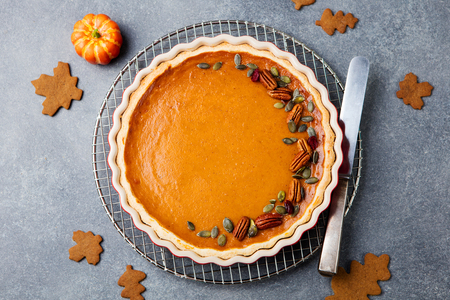 pecan pie: Tasty pumpkin pie, tart made for Thanksgiving day in a baking dish. Grey stone background. Top view Foto de archivo