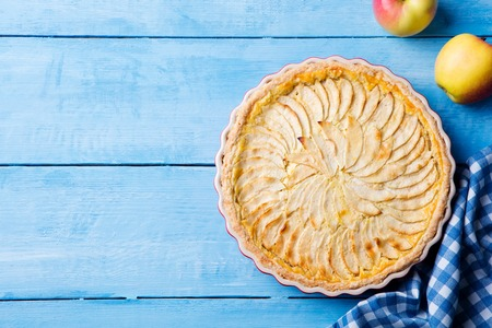 Apple pie with cream on a blue wooden background. Top view. Copy space 스톡 콘텐츠