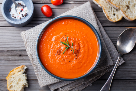 Tomato soup in a black bowl on wooden background. Top view. Copy space Stockfoto