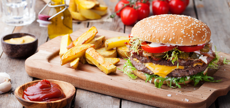 Hamburguesa, hamburguesa con patatas fritas Tabla de cortar. Foto de archivo