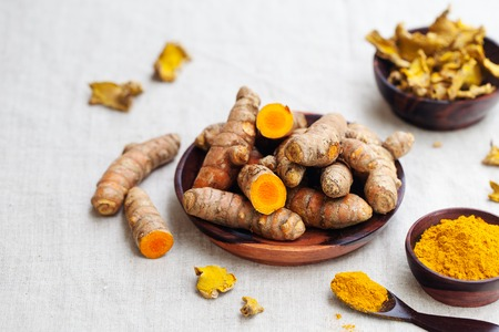 Fresh and dried turmeric roots in a wooden bowl.