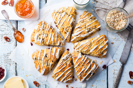 Scones with oats, cranberry and pecan nuts on wooden background. Top view. Imagens