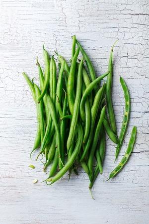 ひびの入った白い木製の背景に緑色の豆。平面図です。 写真素材