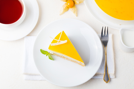 Passion fruit cake, mousse dessert on a white plate with cup of tea. Top view Stock Photo