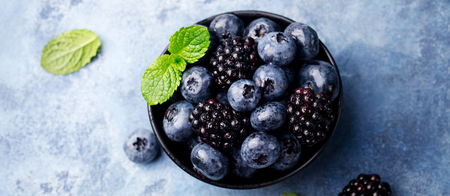 Fresh blueberry and blackberry berries with mint leaves in black bowl on blue stone background. Top view. Copy space.