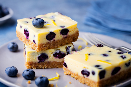 Blueberry cake, cheesecake on a grey plate on blue stone background.