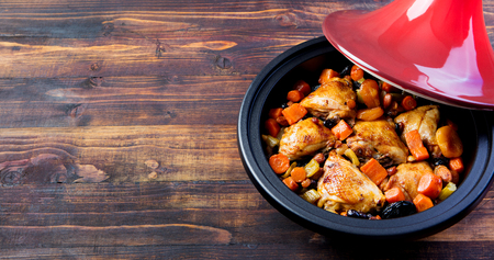 Tagine with cooked chicken, vegetables. Copy space Stock Photo - 77466462