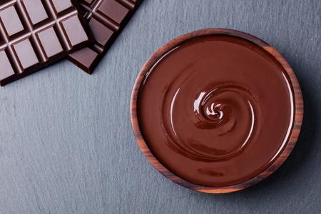 Gesmolten chocolade en reepjeschocolade. Leisteen achtergrond. Ruimte kopiëren Bovenaanzicht.