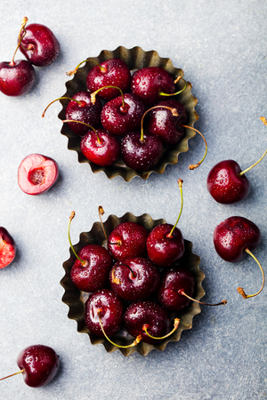 Fresh ripe black cherries in a metal bowl on a stone background. Top view.