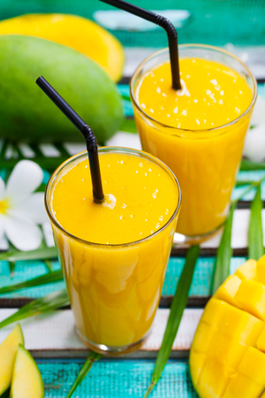 Fresh tropical fruit smoothie mango juice and fresh mango on a outdoor tropical background Stock Photo
