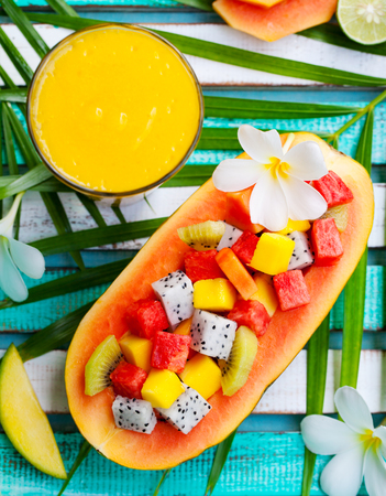 papaya flower: Tropical fruit salad in half of papaya with mango juice, smoothie on colorful wooden background with palm leaf and flowers. Top view. Stock Photo