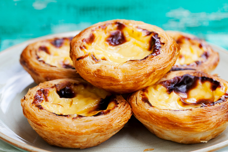 Egg tart, traditional Portuguese dessert, pastel de nata on a plate. Colorful wooden background.